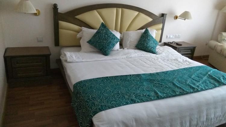 Pandangan katil dalam bilik Century Pines Resort jenis Deluxe